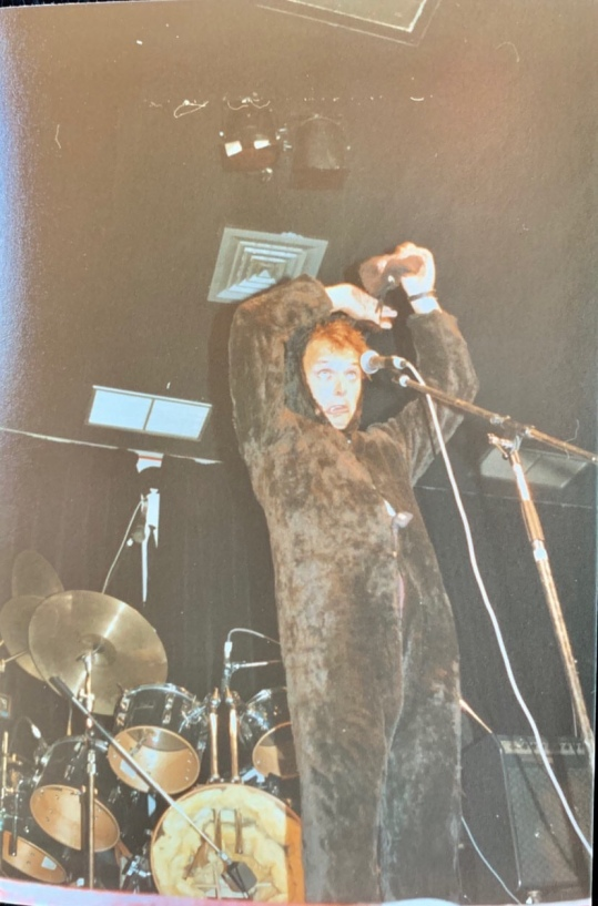 Chris Marks, Rik on stage, rabbit suit, takes off his mask